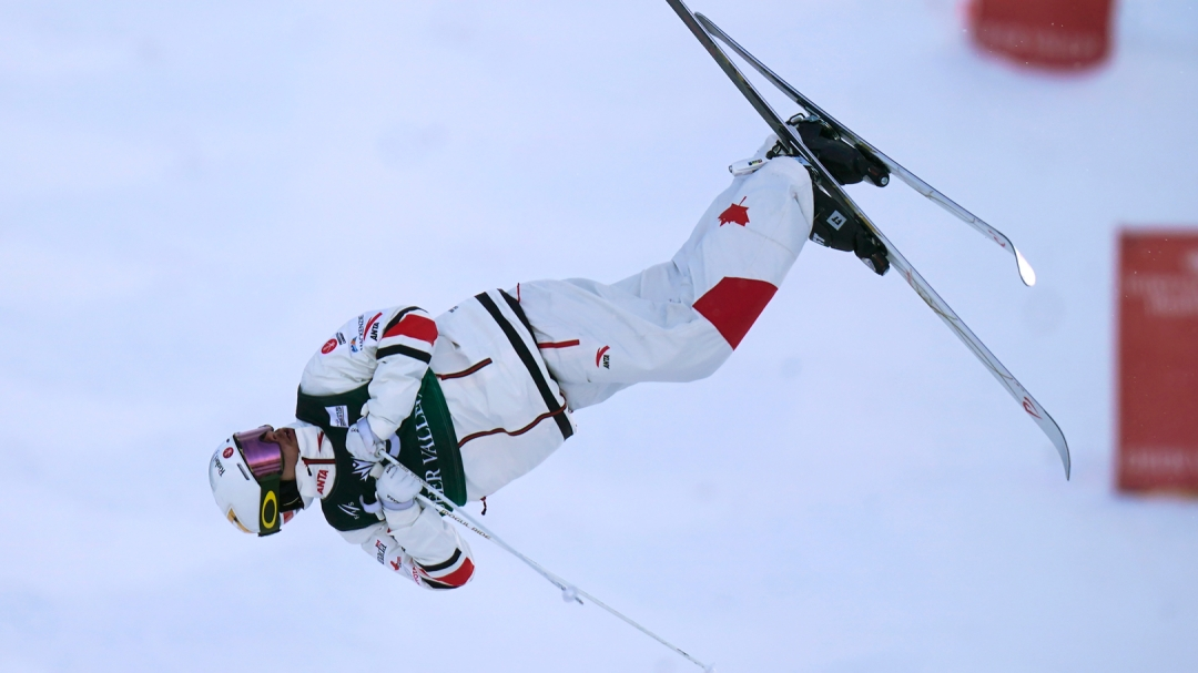 Kingsbury mid-turn in the air, hugs his arms close to his chest while his skis are in the air.
