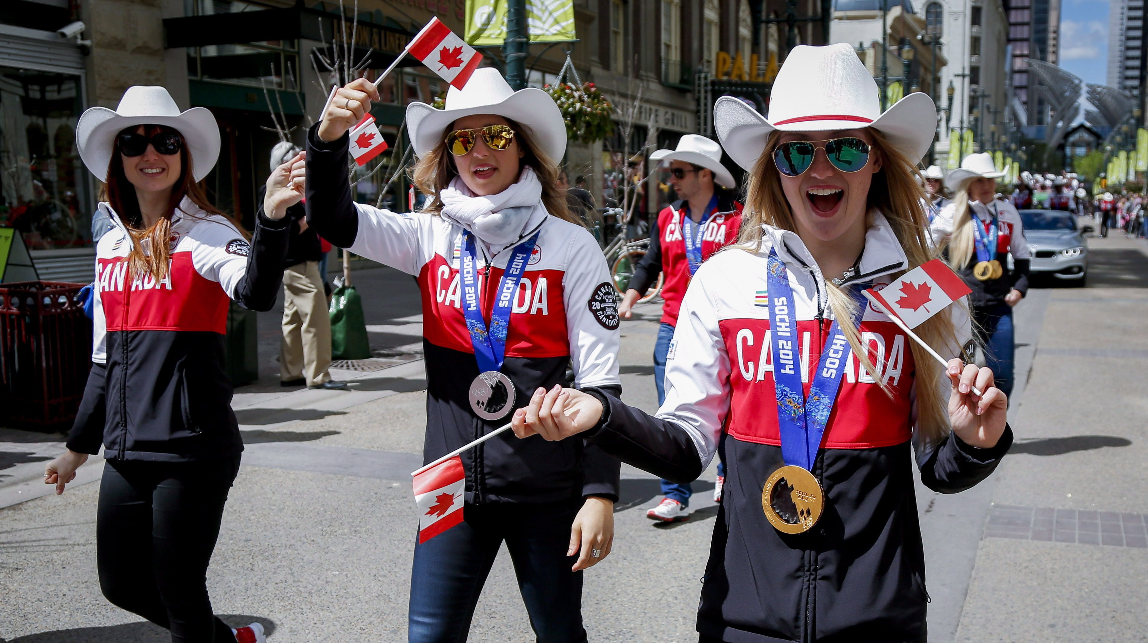 Sochi 2014 Olympians Justine Dufour-Lapointe, right, Chloe Dufour-Lapointe. centre, and Maxime Dufour-Lapointe, take part in a Parade of Champions in Calgary, Alta., Friday, June 6, 2014.