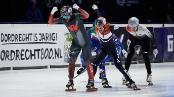 Charles Hamelin raises arms in celebration as he beats his competitors to the finish line
