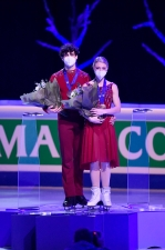 Two figure skaters stand on the podium
