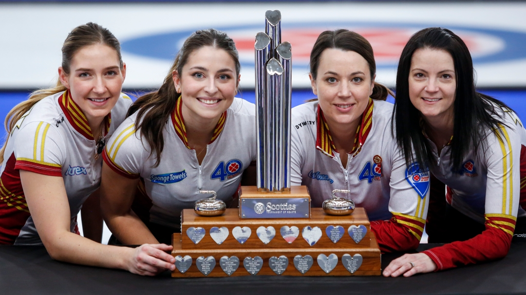 Four curlers pose with the Tournament of Hearts trophy