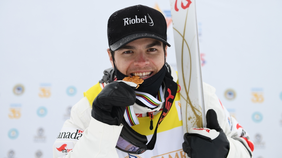 Mikael Kingsbury takes a bite of his world championship gold medal that is shaped like a snowflake.