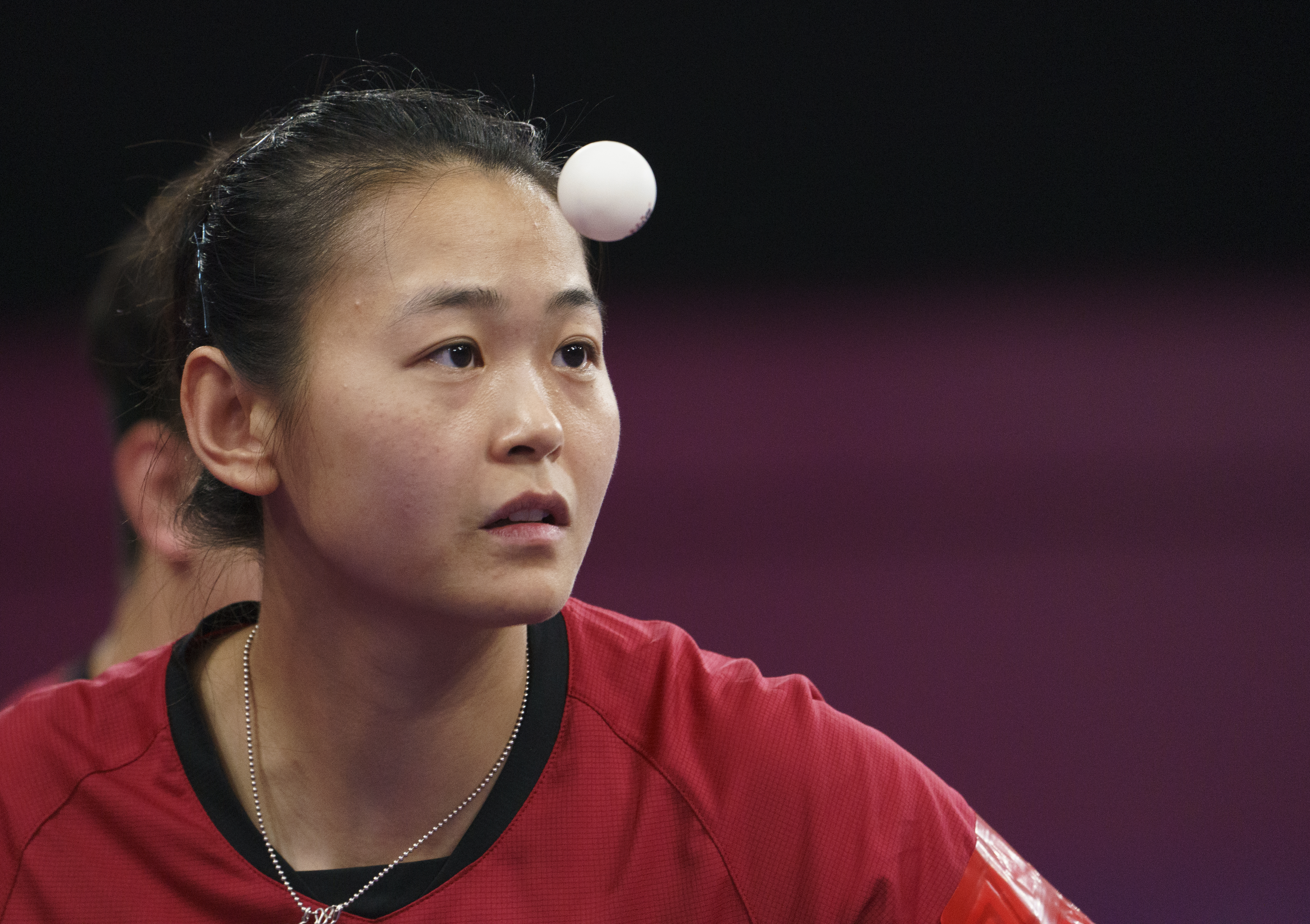 Table tennis ball floats in front of female player