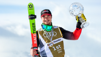 Reece Howden holds up his Crystal Globe in his left hand and his skis in the other.
