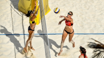 A high angle shot of Sarah Pavan (centre) sends the ball back to Talita Da Rocha during a beach volleyball game.
