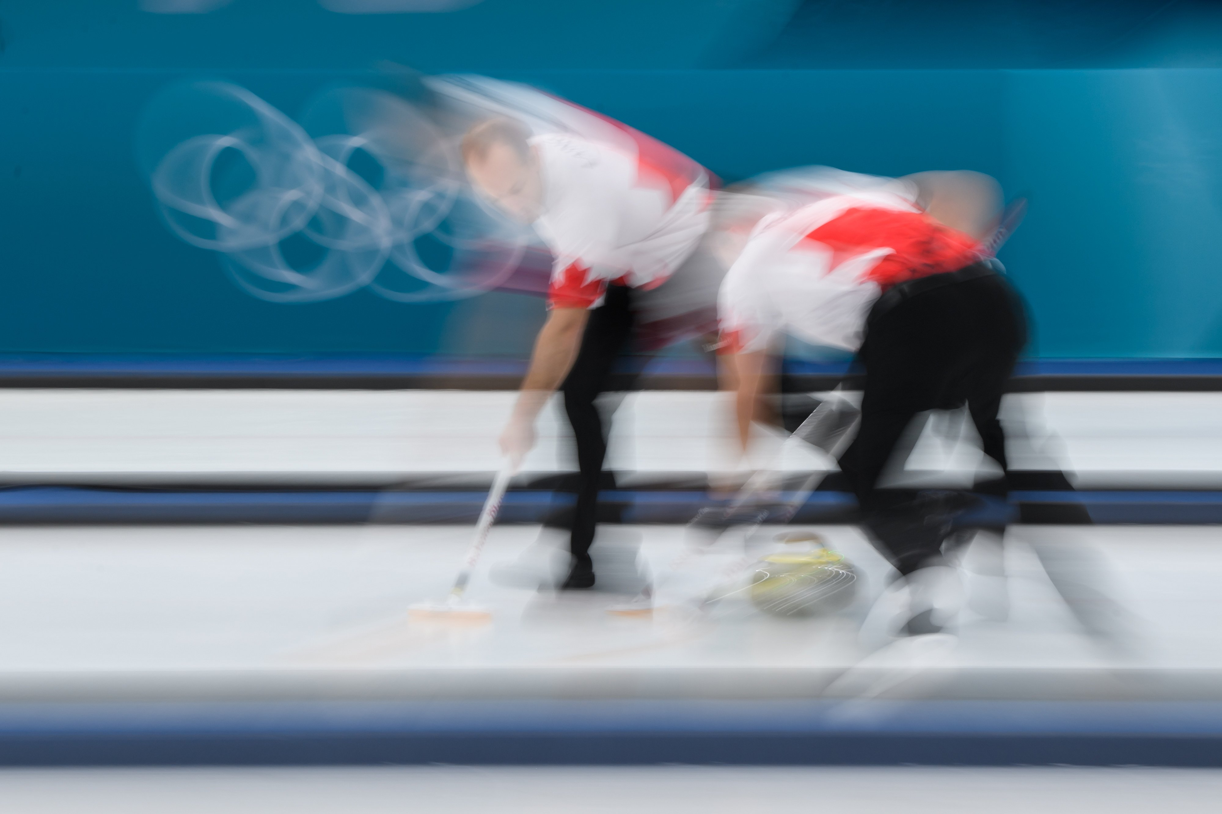 Blurry photo of two curlers sweeping