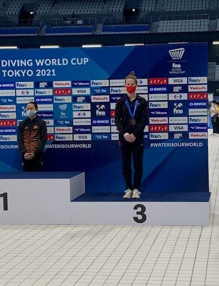 Caeli McKay stands on bronze medal step of podium