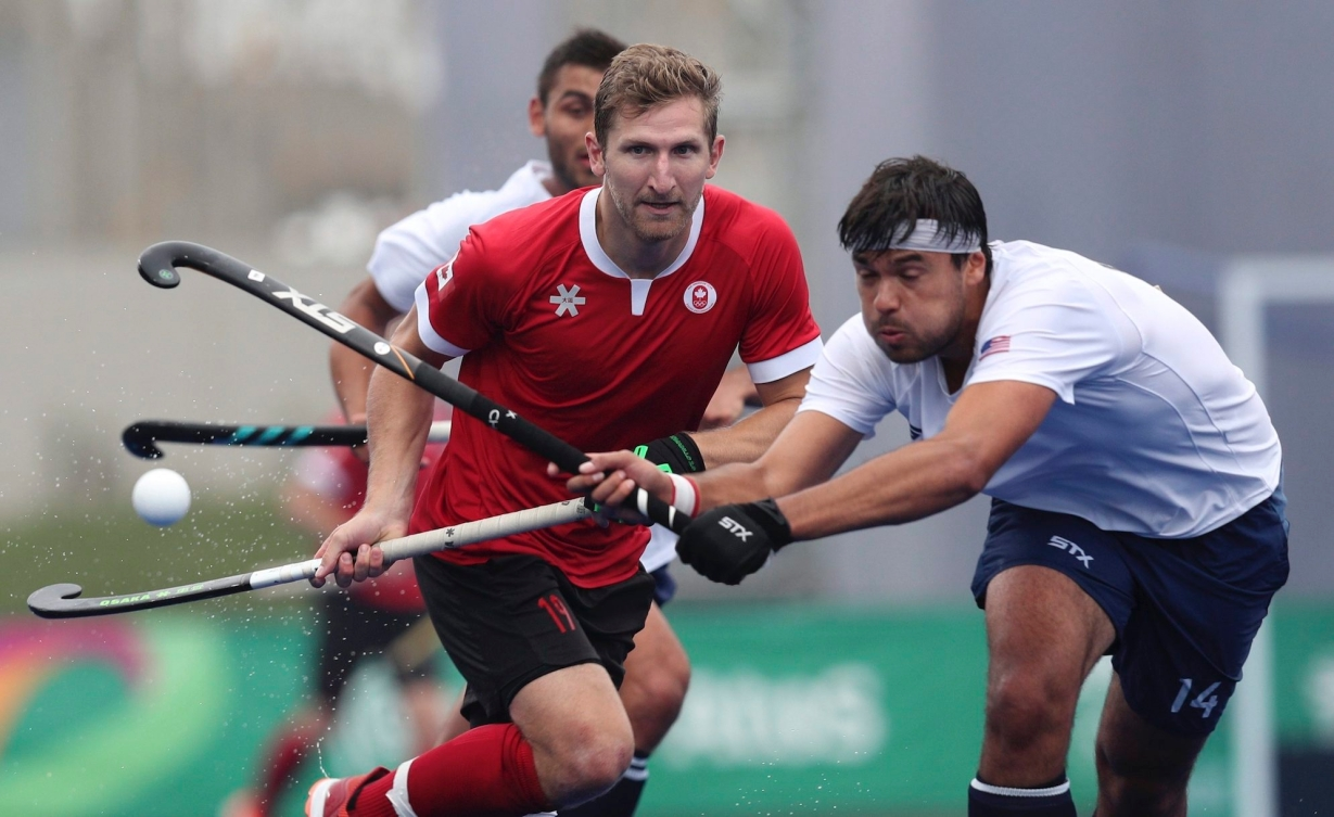 Hans Kaeppeler of the United States, right, and Mark Pearson of Canada compete for control of the ball during the field hockey men's preliminaries group B match at the Pan American Games in Lima, Peru, Thursday, Aug. 1, 2019. (AP Photo/Martin Mejia)