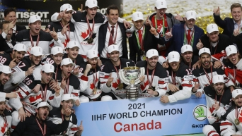 Team Canada hockey players sit together on ice with gold medals and trophy