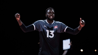 Volleyball player raises arms in celebration
