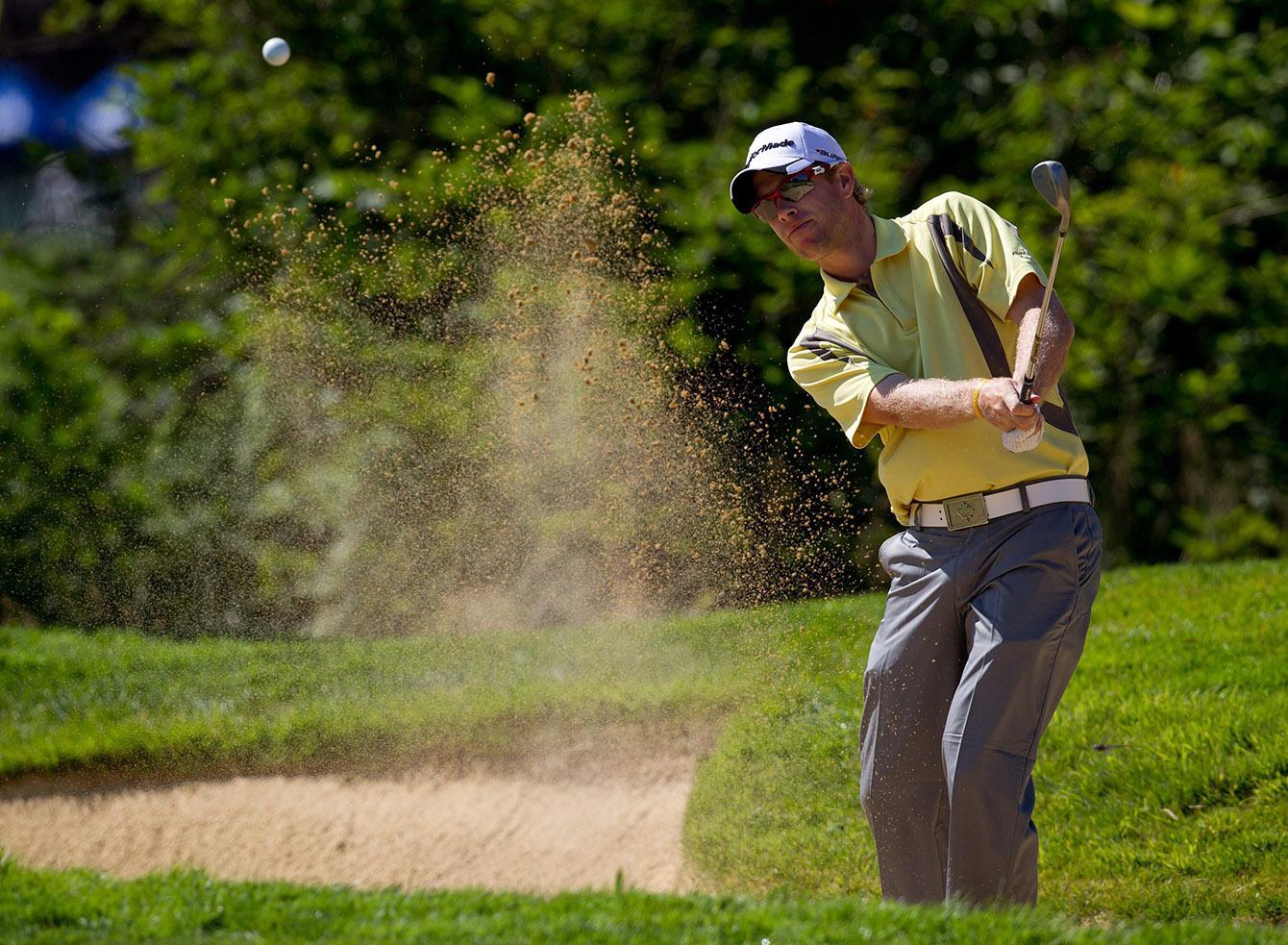 David Hearn frappant sa balle hors de la fausse de sable