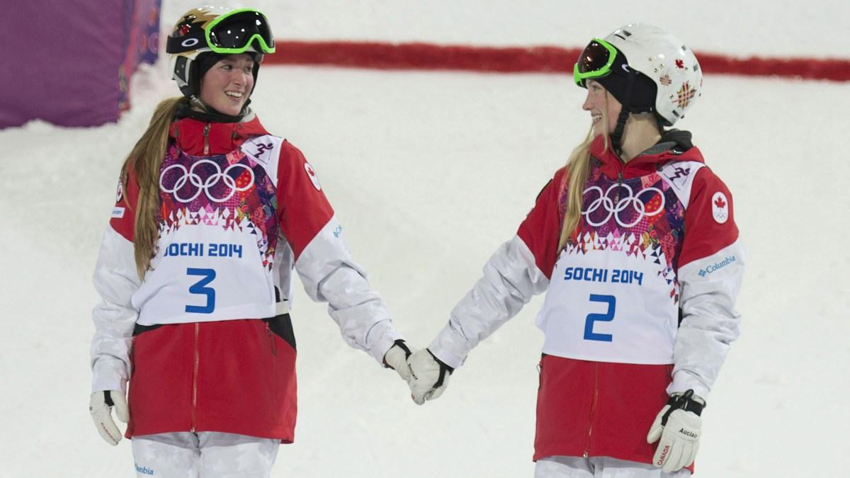Justine (gauche) et Chloé Dufour-Lapointe se tiennent la main sur le podium après avoir remporté respectivement l'or et l'argent aux Jeux olympiques de Sotchi, le 8 février 2014.