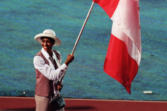 Charmaine Crooks, souriante, portant le drapeau.