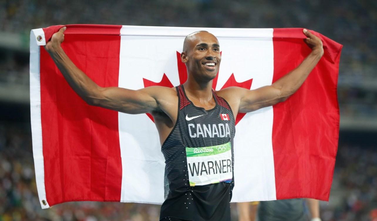 Damian Warner tenant le drapeau canadien