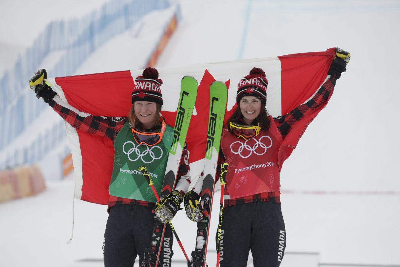 Kelsey Serwa et Brittany Phelan prennent la pause avec le drapeau canadien après avoir remporté l'or et l'argent respectivement à l'épreuve de ski cross féminin des Jeux olympiques de PyeongChang, en Corée du Sud, le 23 février 2018.
