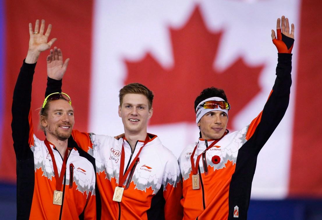 Ted-Jan Bloemen, à gauche, et ses coéquipiers Benjamin Donnelly et Jordan Belchos célèbrent leur médaille d'or après l'épreuve de poursuite par équipes à la Coupe du monde de l'ISU à Calgary, le 14 novembre 2015. LA PRESSE CANADIENNE/Jeff McIntosh