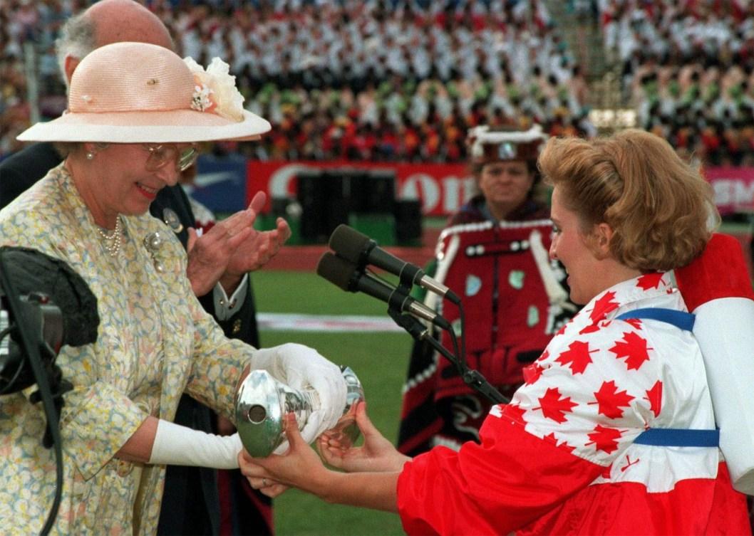 La médaillée d'or Myriam Bedard tient la main de la Reine Elizabeth II lors de la cérémonie d'ouverture des Jeux du Commonwealth de 1994, à Victoria. (CP PHOTO/Andrew Vaughan)