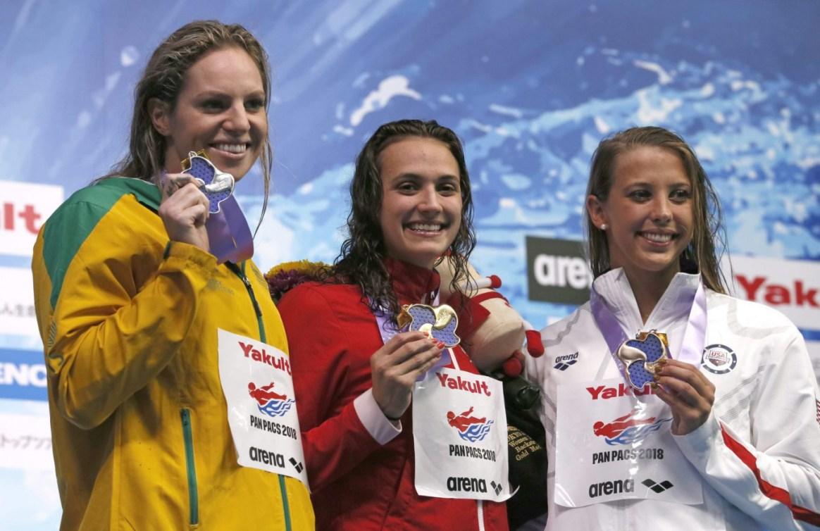 Kylie Masse, au centre, célèbre sur le podium après avoir gagné au 100 m dos en compagnie de Emily Seebohn, à gauche, et de Kathleen Baker, à droite, aux Championnats pan-pacifiques à Tokyo. Vendredi 20 août 2018. (AP Photo/Koji Sasahara)