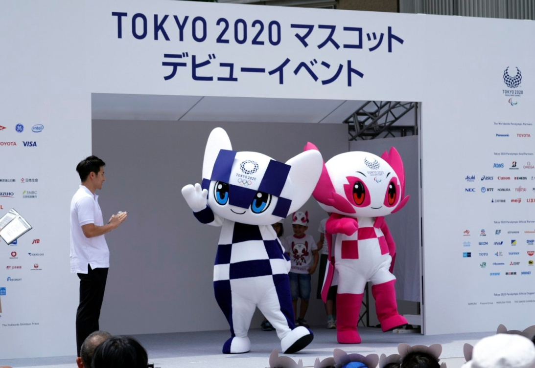 Les deux mascottes saluent la foule sur la scène.